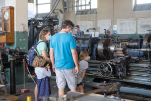 Familie betrachtet eine Drehmaschine