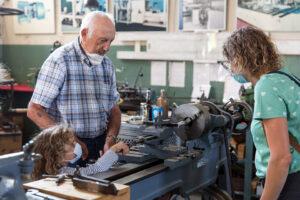 Kind an der Drehmaschine mit Herrn Böhringer